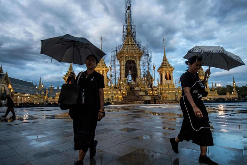 Workers carry umbrellas as they walk away from the cremation site for Thailand's late king Bhumibol Adulyadej, on Oct 17, 2017.