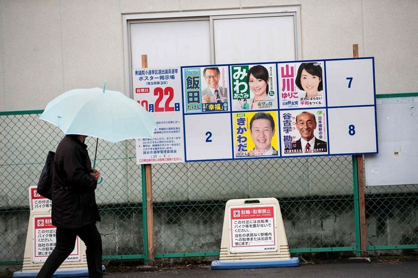A man walks past electoral posters of Japanese candidates for the upcoming general election in Koshigaya city, Saitama prefecture, on Oct 20, 2017.