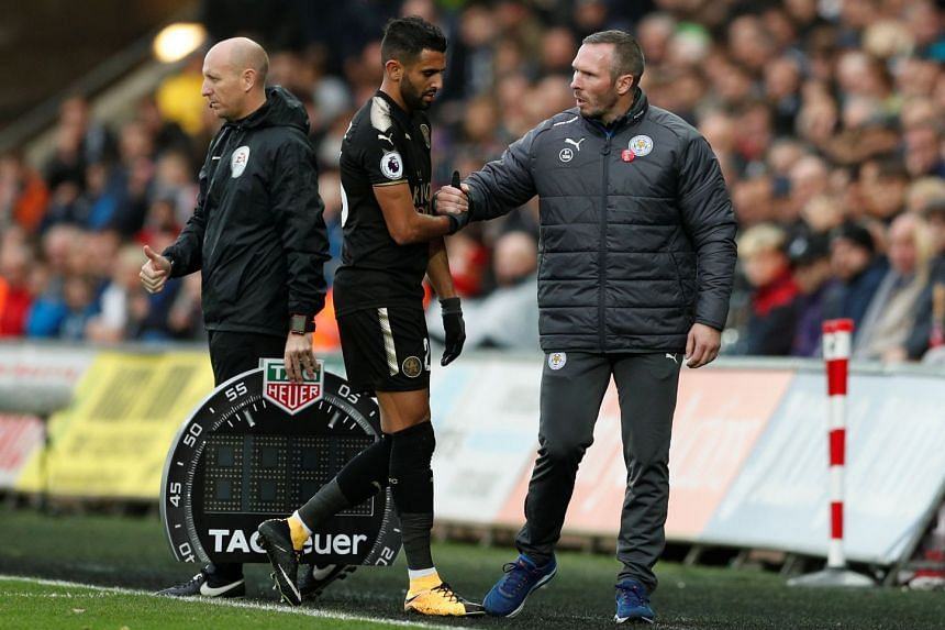 Leicester City caretaker manager Michael Appleton shakes hands with Leicester City's Riyad Mahrez as he is substituted.