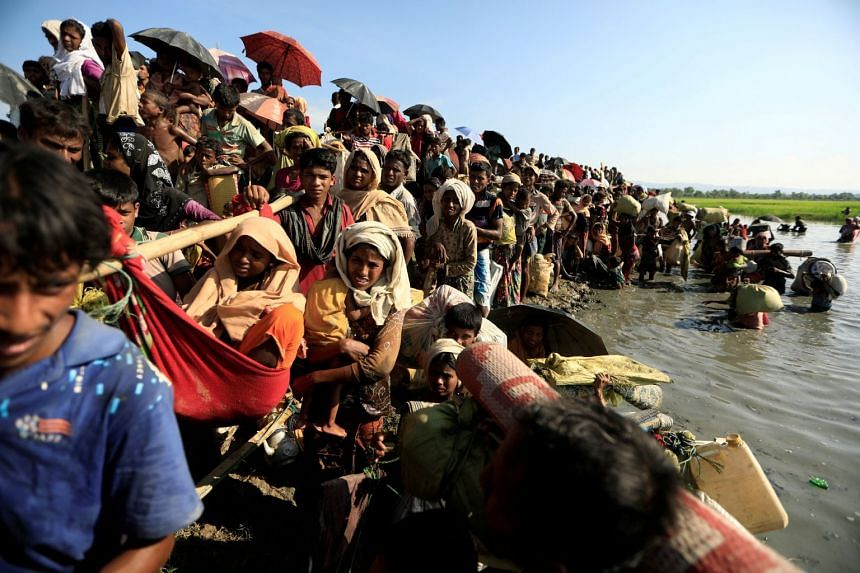 Rohingya refugees who fled from Myanmar wait to be let through by Bangladeshi border guards after crossing the border in Palang Khali, Bangladesh, on Oct 16, 2017.