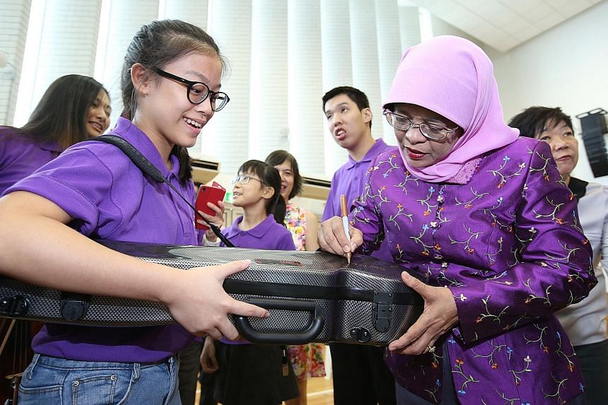 Dressed in purple, President Halimah Yacob signed autographs and chatted with over 60 musicians of the Purple Symphony yesterday, to encourage them as they prepared for an upcoming concert. The musicians, some of whom have special needs, will be perf