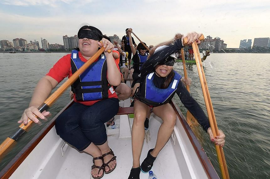 Financial consultant Andrea Bein (at right), 33, and Singapore Management University student Ong Hui Xin, 23, paddling down the Kallang River in a dragon boat while blindfolded yesterday afternoon. The activity was part of the See The True Me campaig