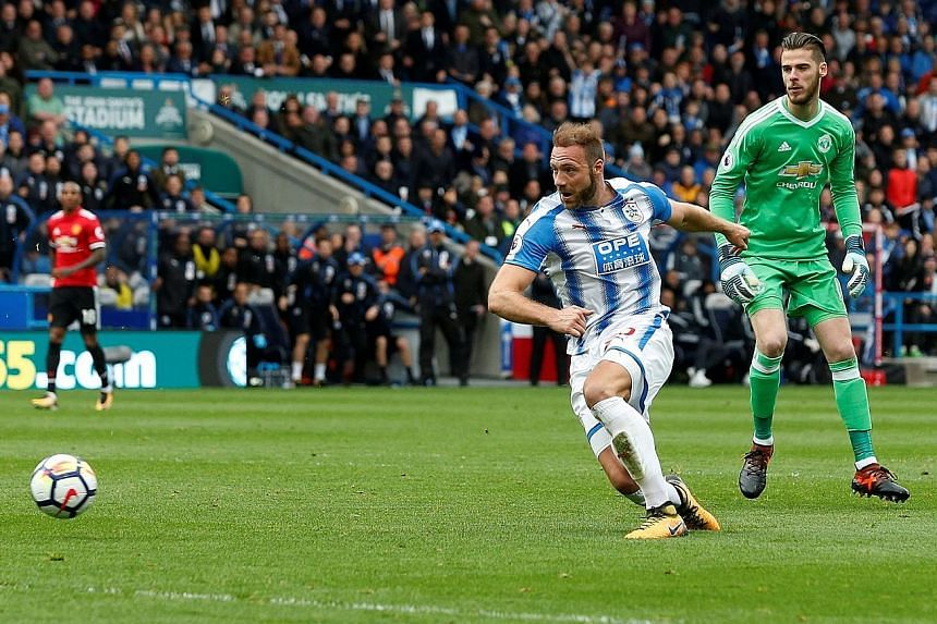 Huddersfield's Laurent Depoitre rounds Manchester United goalkeeper David de Gea to double his side's lead. The last time Huddersfield recorded a win over their illustrious opponents was in 1952.