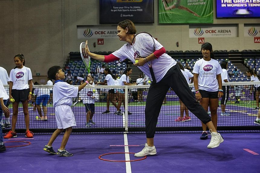 WTA Finals ambassador Lindsay Davenport, a three-time Grand Slam singles champion, high-fiving Adam Sharin, who took part in the WTA Charities Community Day at OCBC Arena yesterday.