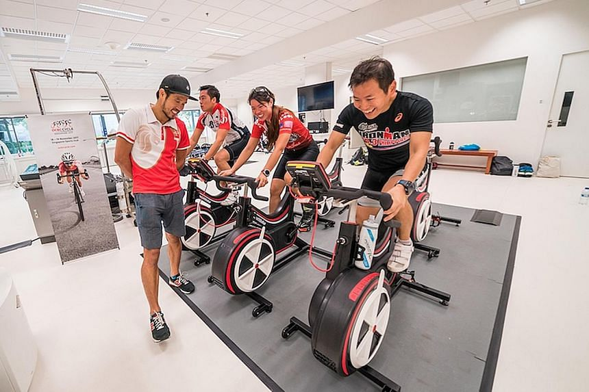 Singapore Cycling Federation head coach Adrian Ng monitoring the power output of workshop participants (from left) Han Ee Kwang, Amelia Chua and Norikazu Yokoyama at the Singapore Sports Institute.