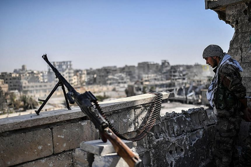 A fighter from the Syrian Democratic Forces standing guard in Raqqa last Friday. The city, which was a stronghold of the Islamic State in Iraq and Syria, was retaken last week by the United States-backed forces.