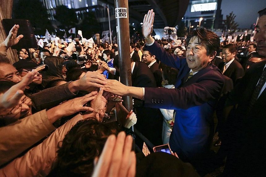 """Japanese Premier Shinzo Abe greeting voters on the final day of the campaign outside the Akihabara rail station in Tokyo yesterday. A two-thirds """"supermajority"""" in the Lower House will help pave the way for Mr Abe to realise his grandiose ambition of"""