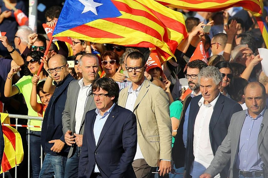 Catalan President Carles Puigdemont (in front) arriving at a demonstration in Barcelona yesterday organised by pro-independence movements, following the imprisonment of two of their leaders - Jordi Sanchez and Jordi Cuixart.