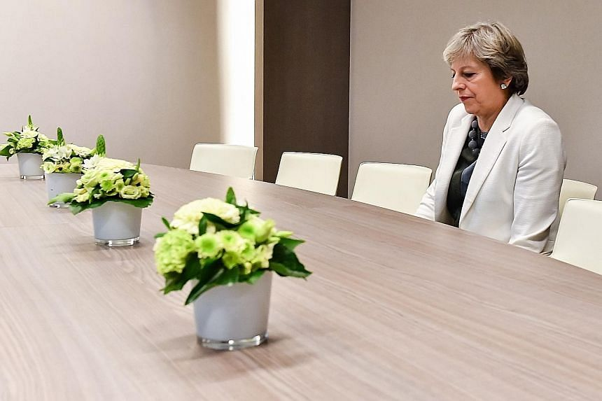 """Social media on Friday mocked embattled British Prime Minister Theresa May over a photograph of her sitting alone in a room awaiting EU Brexit talks, calling it a """"metaphor"""" for her isolated position. In the viral snap, May is seen alone at a large t"""