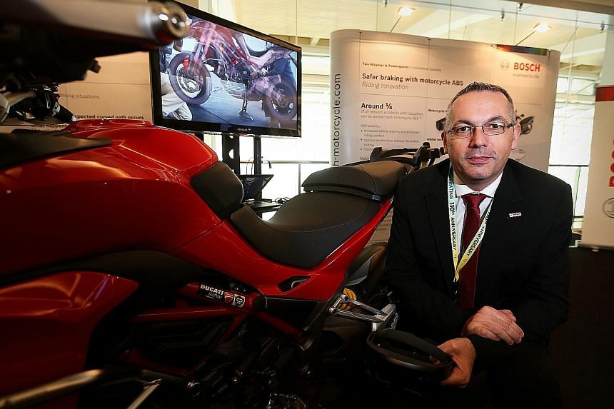 Mr Klaus Landhaeusser at a display showing how virtual reality and augmented reality can help mechanics and technicians learn about the systems used in motorcycles like the Ducati Multistrada above. In the background is an X-ray model of the Ducati b