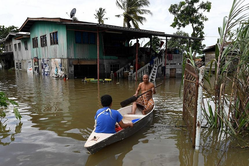 Villagers of Kampung Taun Gusi in Kota Belud making their way home in a sampan after four days of continuous heavy rain. Many areas in Sabah are flooded, with Kota Belud being the worst hit.