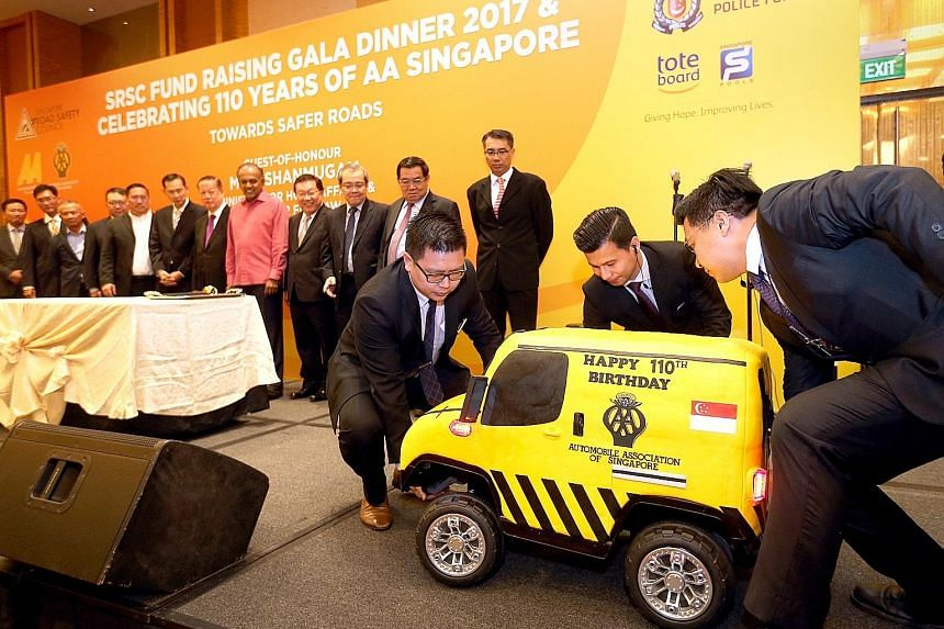 The 110kg Automobile Association cake being carried on stage at the dinner event yesterday. It was cut by Mr K. Shanmugam (in pink) and members of the SRSC.
