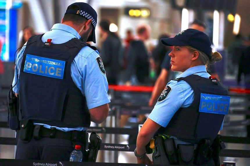 Australian Federal Police officers stand near the check-in counters at the Sydney Airport Domestic terminal in Australia, on July 30, 2017.