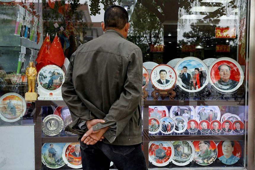 Souvenir plates with images of Chinese late Chairman Mao Zedong and Chinese President Xi Jinping are seen at a shop during the ongoing 19th National Congress of the Communist Party of China, in Beijing.