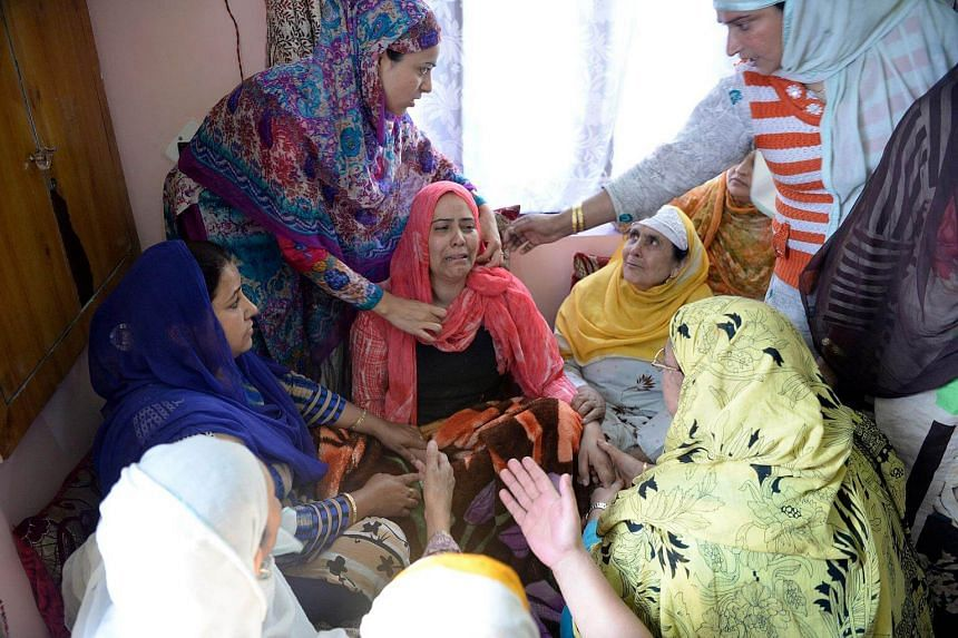 Kashmiri resident Tasleema (right), and the victim of a 'braid chopping', reacts as she is surrounded by relatives and neighbours in the Batamaloo area of Srinagar.