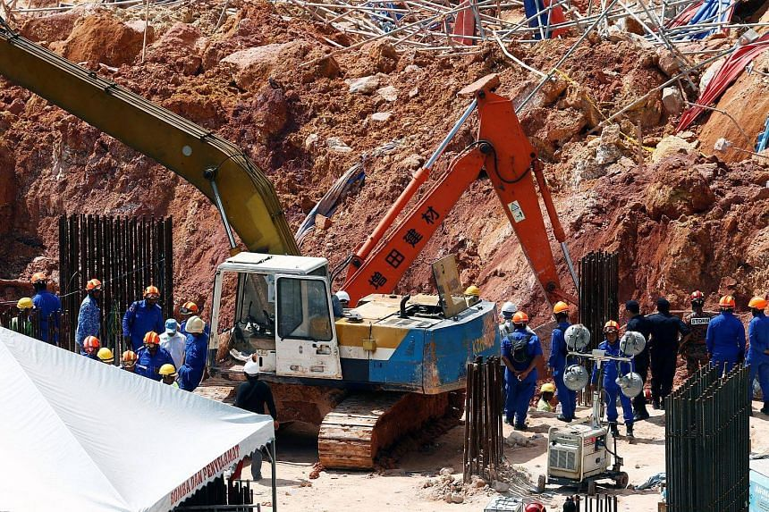 Rescues workers search for victims of a landslide at a construction site in Tanjung Bungah.