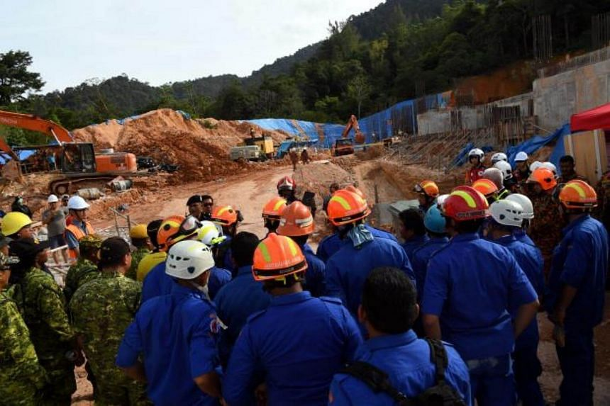 Rescue workers are seen at a construction site after it was hit by a landslide in Tanjung Bungah.