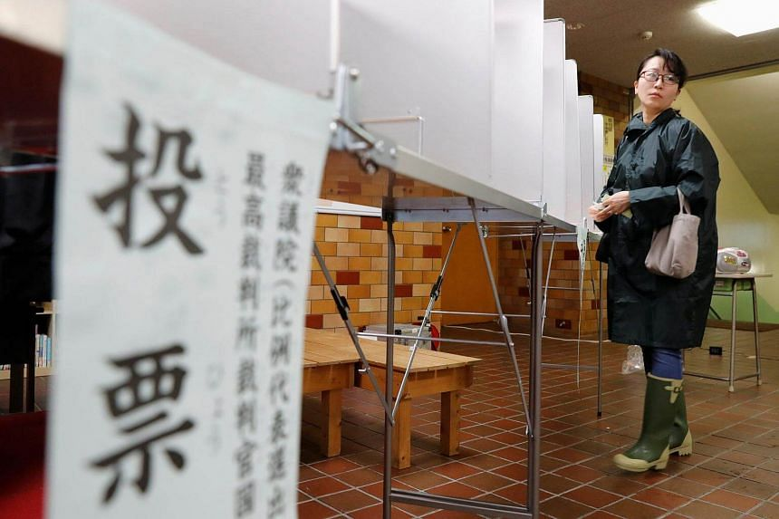 A woman fills out her ballot for a national election at a polling station in Tokyo, on Oct 22, 2017.