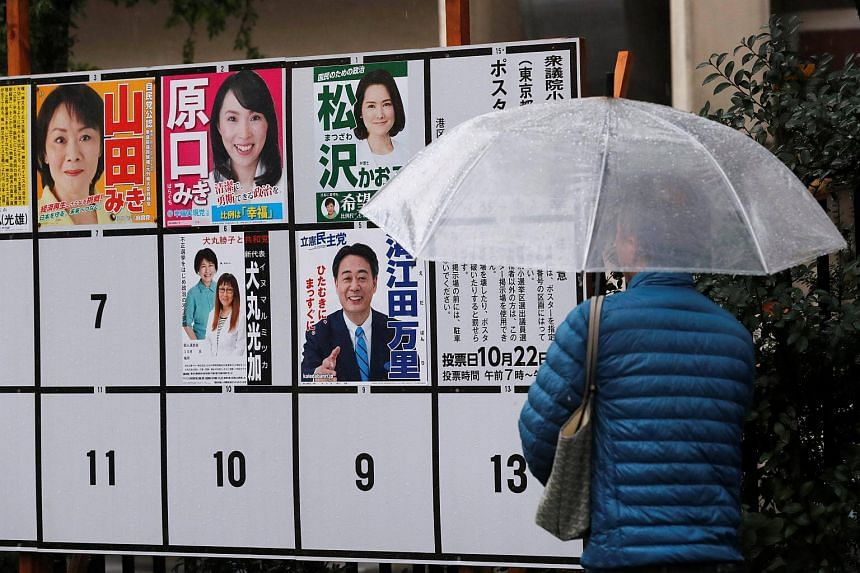 A man looks at election posters nearby a polling station in Tokyo, on Oct 22, 2017.