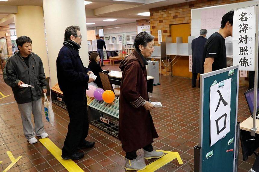 People line up in order to vote for a national election at a polling station in Tokyo, on Oct 22, 2017.