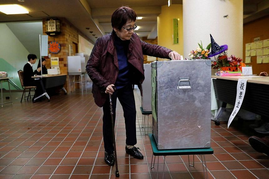 A woman casts her ballot for a national election at a polling station in Tokyo, on Oct 22, 2017.