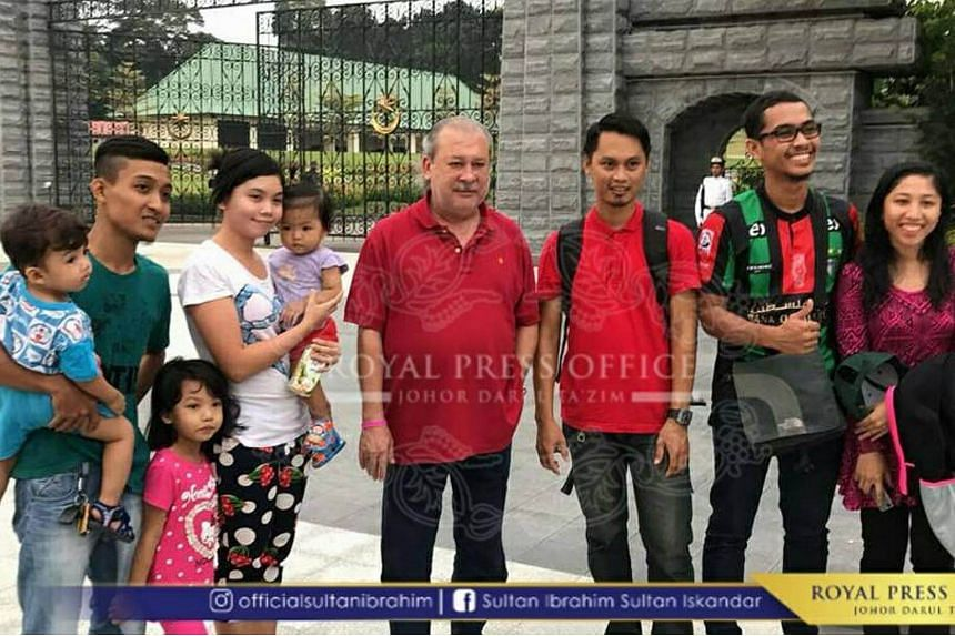 Sultan Ibrahim (in red) poses for a photograph with people outside Istana Bukit Serene in Johor Baru.