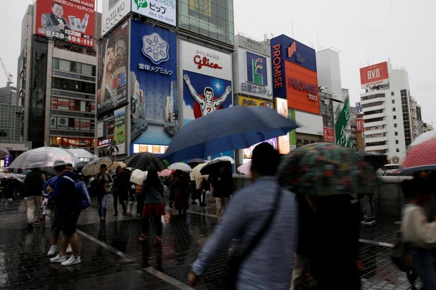 Shoppers walk under umbrellas as Typhoon Lan approaches Japan's mainland, in Osaka, western Japan, on Oct 22, 2017.