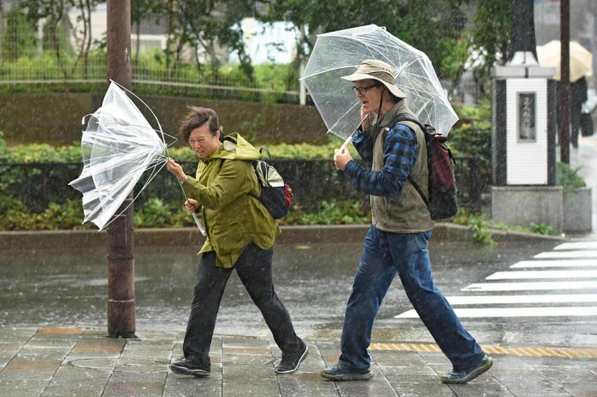 A woman struggles with her umbrella in the strong wind in Tokyo on Oct 22, 2017.