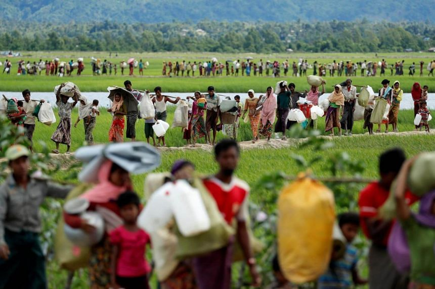 Rohingya refugees, who crossed the border from Myanmar two days before, walk after they received permission from the Bangladeshi army to continue on to the refugee camps, in Palang Khali, near Cox's Bazar, Bangladesh on Oct 19, 2017.