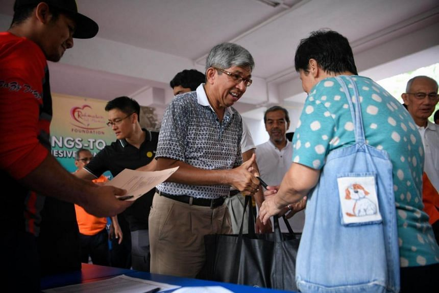 Minister-in-charge of Muslim Affairs and Minister for Communications and Information, Dr Yaacob Ibrahim helps distribute household groceries to needy residents of Champions Way as part of Rahmatan lil 'Alamin (RLA) Day.