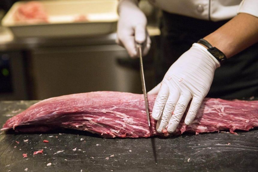 A chef slices a piece of Wagyu beef inside the kitchen at a members only restaurant operated by Wagyumafia in Tokyo, Japan, on Sept 28, 2017.