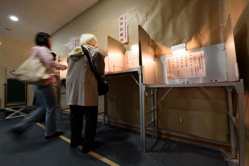Voters walk towards voting booths at a polling station during a general election in Tokyo, Japan, on Sunday, Oct. 22, 2017. More than 100 million voters began casting ballots today in an election that may clear the way for Prime Minister Shinzo Abe t