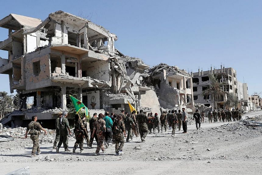 Syrian Democratic Forces fighters marching past destroyed buildings while celebrating Raqqa's liberation from ISIS militants.