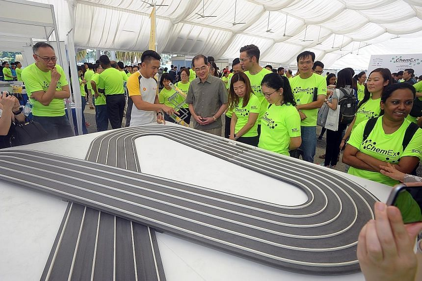 Mr Lim Hng Kiang (in grey) at a Shell electric car exhibit on Saturday at ChemEx, an annual event organised to raise awareness of career opportunities in the energy and chemicals industry.