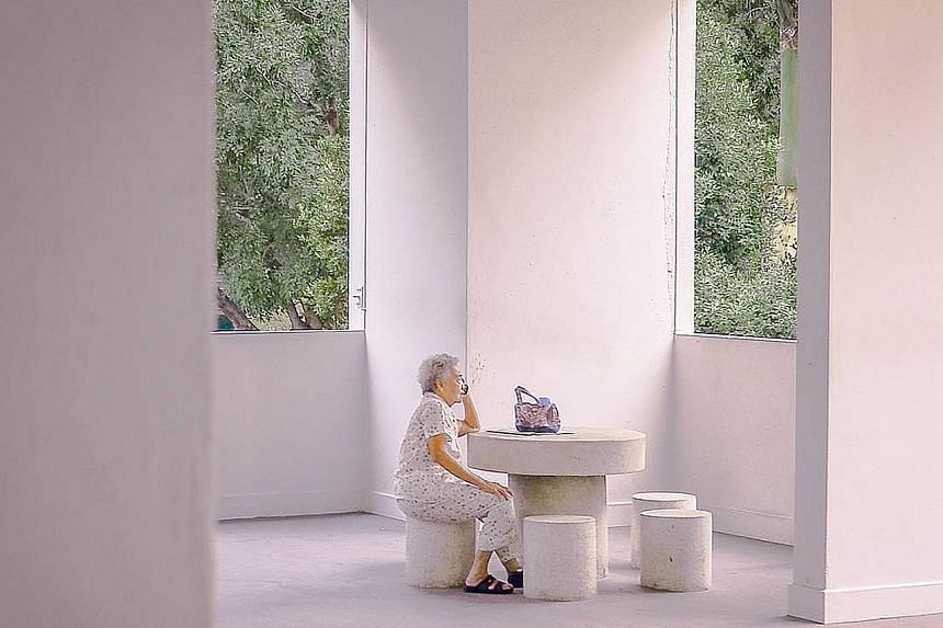 """Entrepreneur James Lum took this winning photo of an old woman at a void deck talking on her phone. He said: """"I came across this old lady alone. The void deck is a very uniquely Singapore feature, and so are her vintage clothes. I wanted to capture t"""