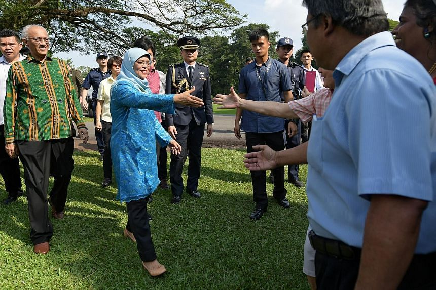 Above: President Halimah Yacob with Marsiling resident Jainah Awang, 68, one of about 80 residents from Marsiling-Yew Tee GRC whom the President met at the Istana open house yesterday. Madam Halimah was an MP in the GRC before she resigned to run for