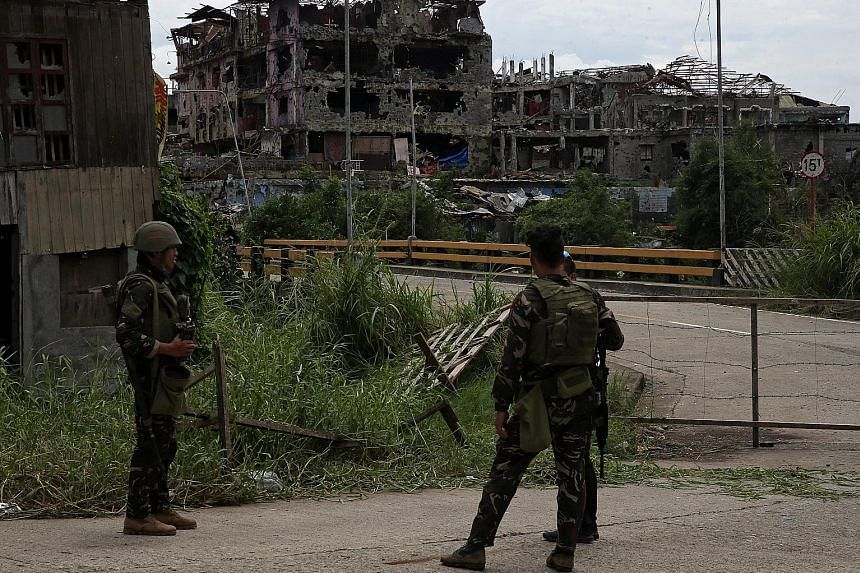 Above: Soldiers standing guard after troops cleared the area of pro-ISIS militants inside the war-torn area of Saduc Proper in Marawi, in the southern Philippines yesterday. Left: A local government worker putting up a sign in the same area in Marawi