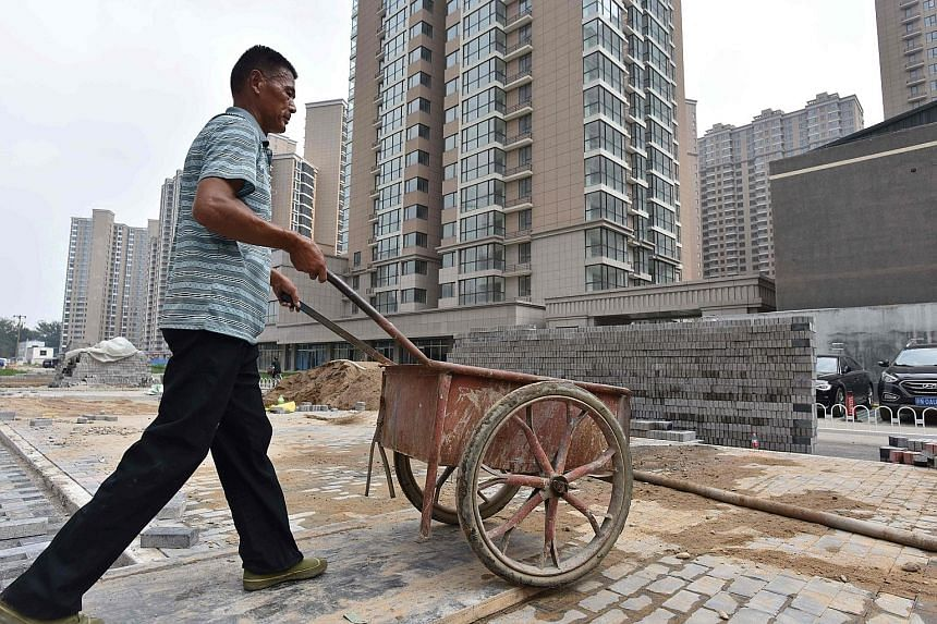 Chinese Housing Minister Wang Menghui (above) says Beijing will not waver in its efforts to regulate the property market and has no intention of loosening control measures, in a sign that the housing market is still being closely watched. Right: A wo