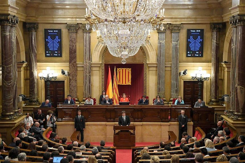 A file photo of Catalan regional government president Carles Puigdemont (centre) giving a speech at the Catalan regional Parliament in Barcelona, on Oct 10, 2017.