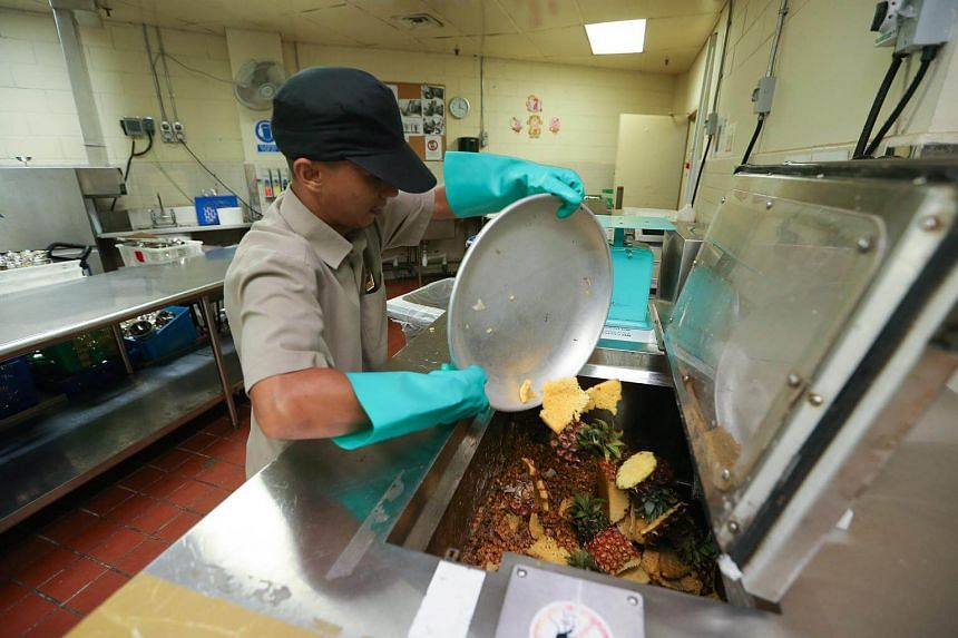 An employee at Fairmont Singapore emptying food waste into a recycling machine.