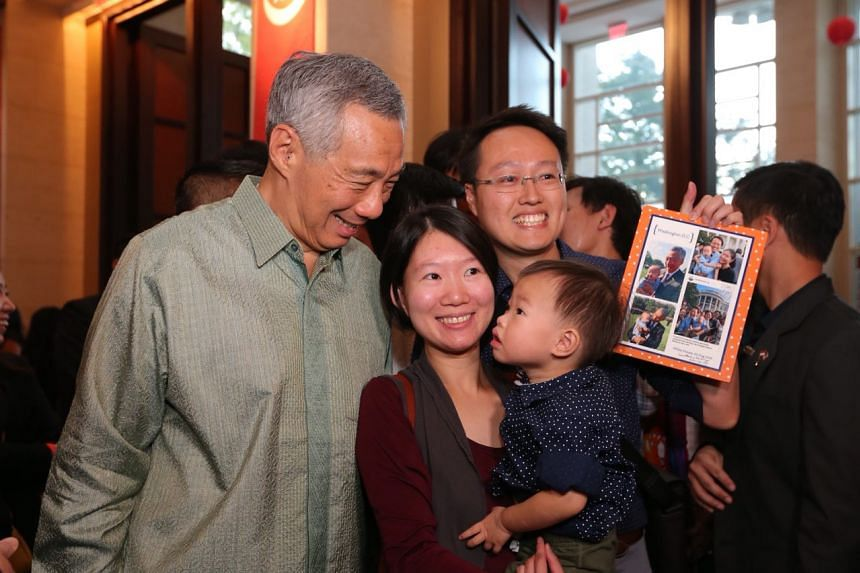 PM Lee with Mr Eric Cheung, 33, Ms Crystal Lim, 30, and their son Dayton Cheung, 2. Mr Cheung is holding framed photos of Dayton being photographed with PM Lee and President Obama during a visit by PM Lee to US last year.