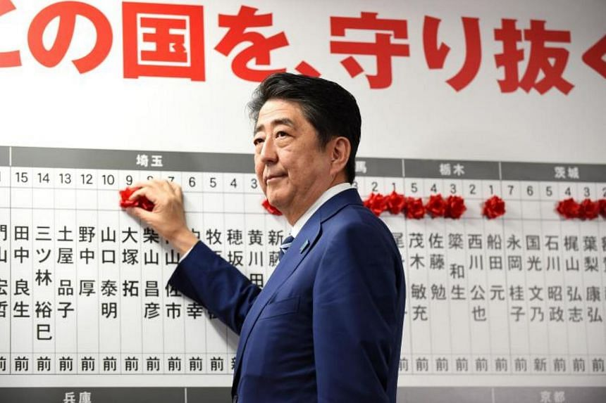 Japan's Prime Minister and ruling Liberal Democratic Party leader Shinzo Abe puts rosettes by successful general election candidates' names on a board at the party headquarters in Tokyo on Oct 22, 2017.