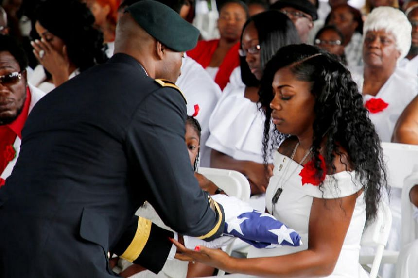 Myeshia Johnson, wife of US Army Sergeant La David Johnson, receives the flag which draped his coffin at a graveside service in Hollywood, Florida, on Oct 21, 2017.