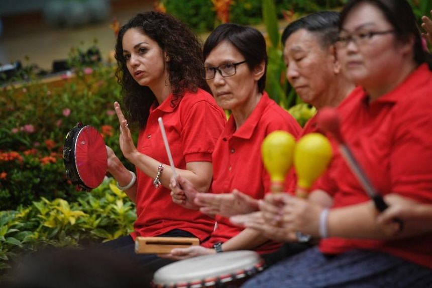 Ms Liliana Garza Covarrubias, 37, the president of the Mexican Association in Singapore, joins other new immigrants, Singaporeans and beneficiaries from Blue Cross Thong Kheng Home in a community percussion ensemble performance at the One Community F