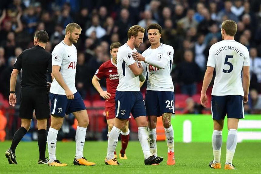 Tottenham Hotspur's English striker Harry Kane (centre) and Tottenham Hotspur's English midfielder Dele Alli celebrate on the pitch after the English Premier League football match between Tottenham Hotspur and Liverpool at Wembley Stadium in London,