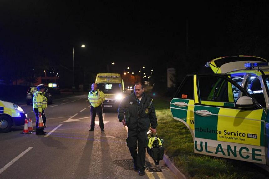 Ambulance crews leave the cordon around the Bermuda Park leisure park in Nuneaton, central England, on Oct 22, 2017.