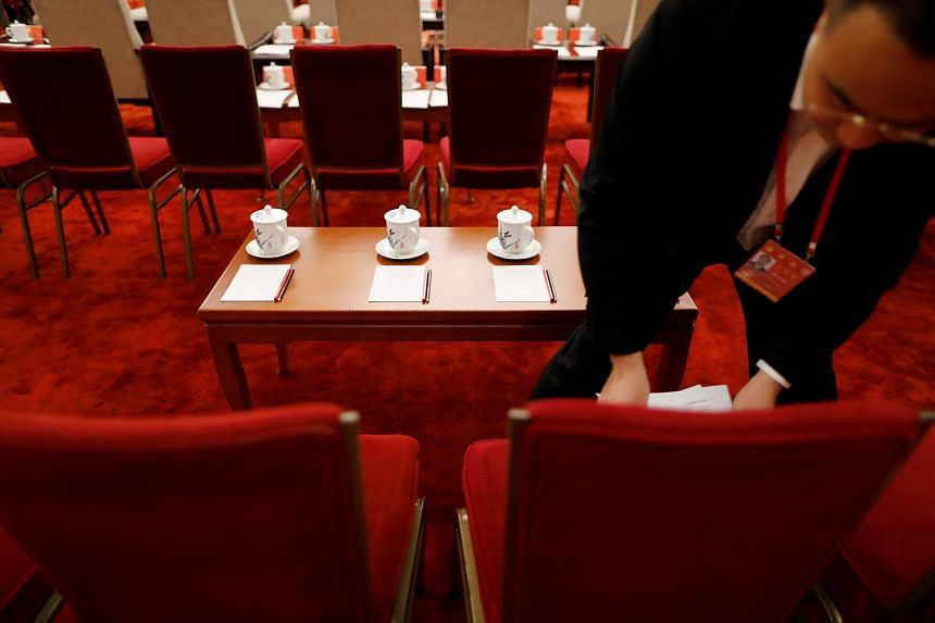 A staff adjusts schedules before a group discussion session on the second day of the 19th National Congress of the Communist Party of China at the Great Hall of the People in Beijing, China, on Oct 19, 2017.