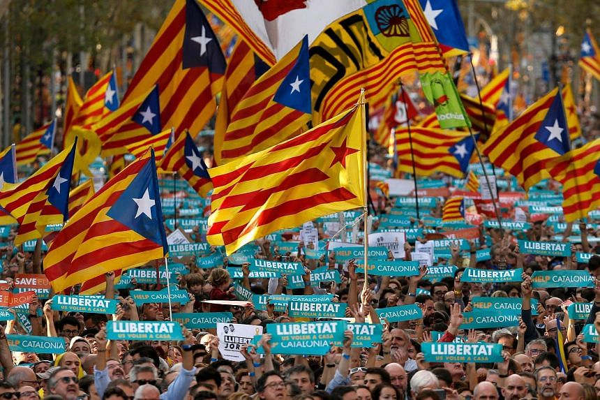 Protesters wave pro-independence Catalan Estelada flags along with signs calling for the release of two separatist leaders during a demonstration in Barcelona on Oct 21, 2017.