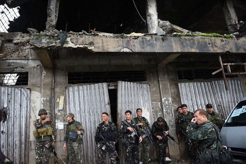 Philippine soldiers standing beside a battle scarred building in what was the main combat area of Marawi on the southern island of Mindanao on Oct 17, 2017.