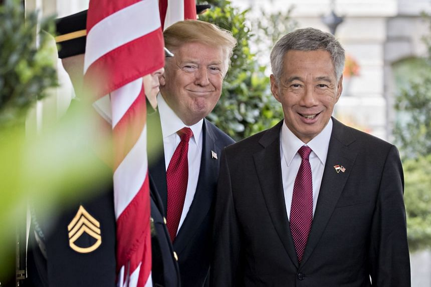PM Lee Hsien Loong and President Donald Trump smile for the cameras before their meeting at the White House on Monday (Oct 23).